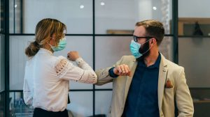 two business people with face masks greeting one another by bumping elbows